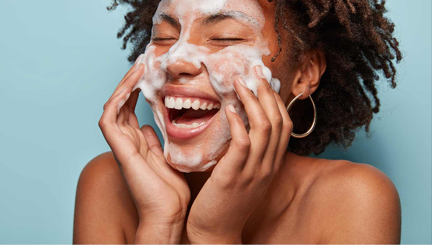 Female model laughing with face covred in a lathered skincare product