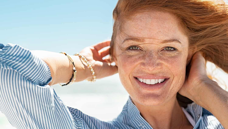 female model applying sunscreen