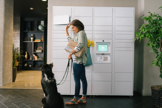 Woman smiling at her dog while retreiving package from Amazon Hub Apartment Locker.