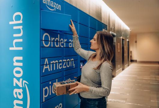 Woman opening a blue Amazon Hub Locker retrieving package.