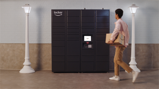 Man carrying package to gray Amazon Hub Apartment Locker.