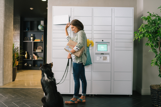 Woman smiling at her dog while retrieving package from Amazon Hub Apartment Locker.