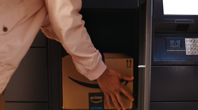 Photo of person reaching into a locker door and retrieving package.