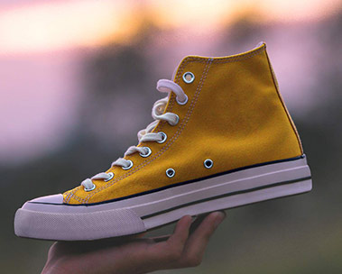 Hand holding up yellow sneaker