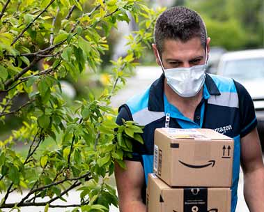 A young male Amazon delivery worker wearing a mask carries boxes from his Amazon Prime delivery van to a customer's door.