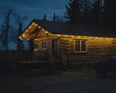 A log cabin on a dark night.