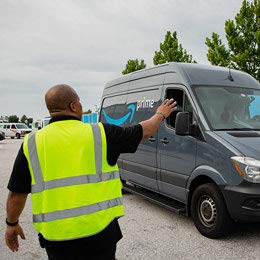 A man in a safety vest waves to someone in a van with the Amazon smile logo.
