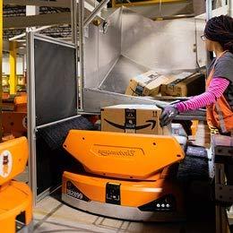 Woman placing a cardboard box on an orange robotic unit.