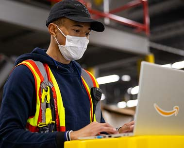 A male Amazon Associate wearing a surgical mask works at his laptop inside an Amazon fulfillment center