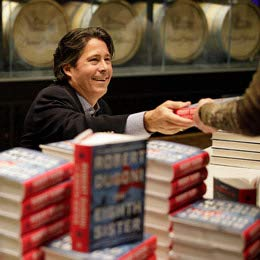 A man sits at a table behind stacks of hardcover books.