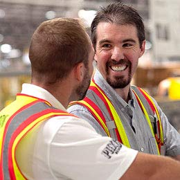 Two men in safety vests stand in a warehouse space.