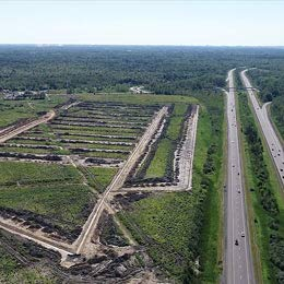 Aerial image of a large empty lot that's been excavated for a building foundation.