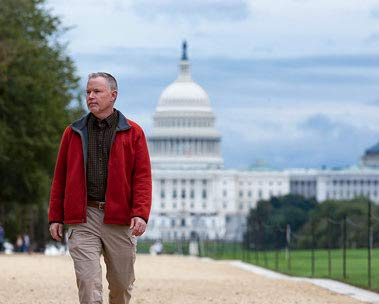 A man walks with the U.S. Capitol in the background.