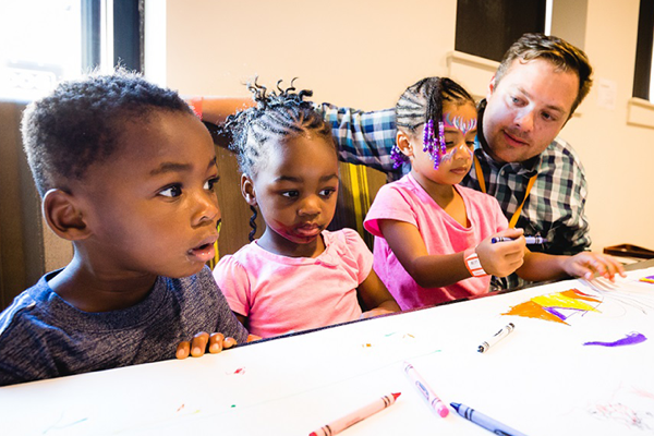 Amazon employee Rob Martin with his three children coloring with crayons at a Friends and Family event in Seattle.