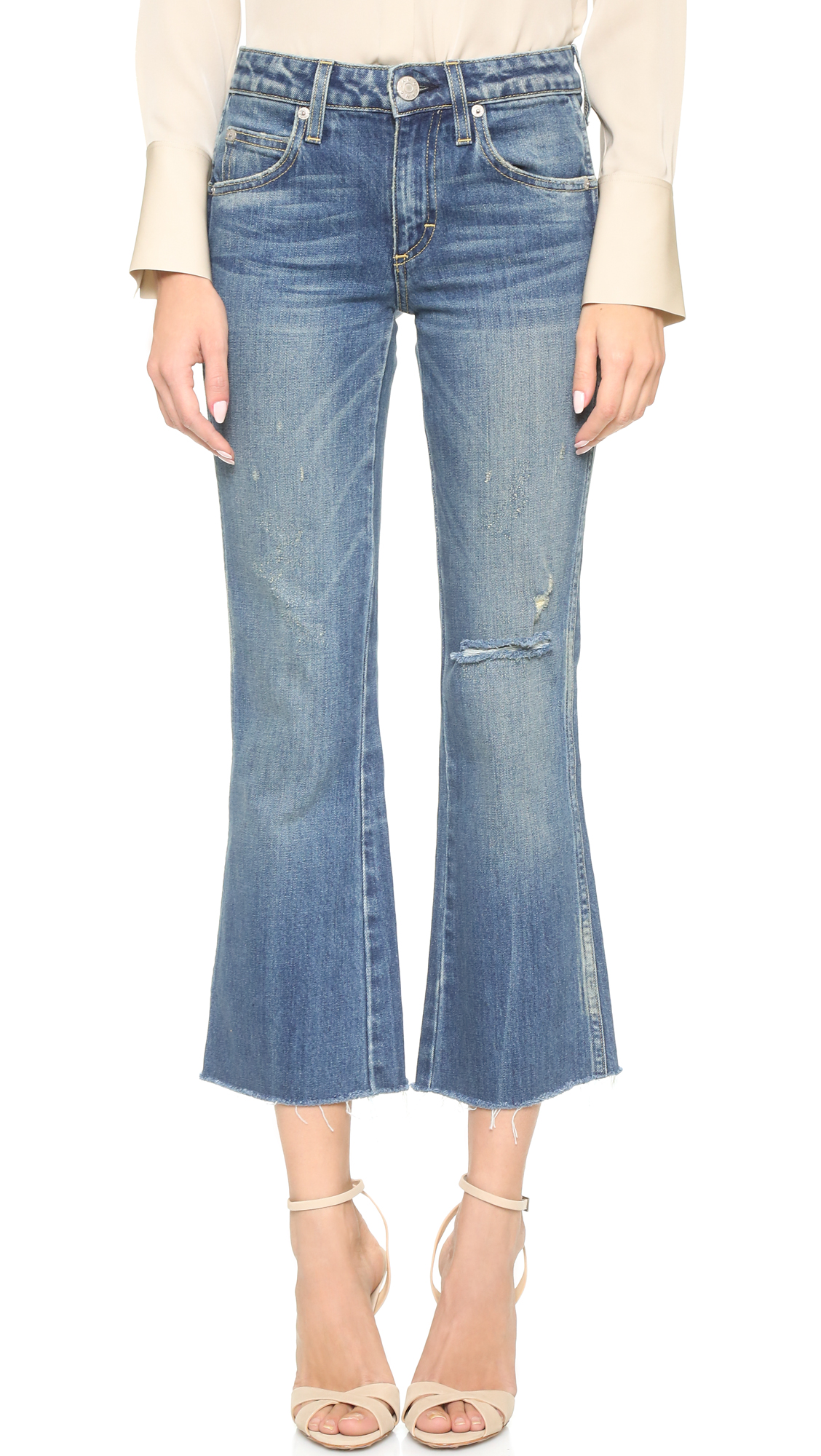 Heavily faded AMO flare jeans have vintage appeal, with a high rise and raw, cropped hems. Shredded holes and frayed spots complement the favorite pair feel. 5 pocket styling. Button closure and zip fly. Fabric: Stretch denim. 98%