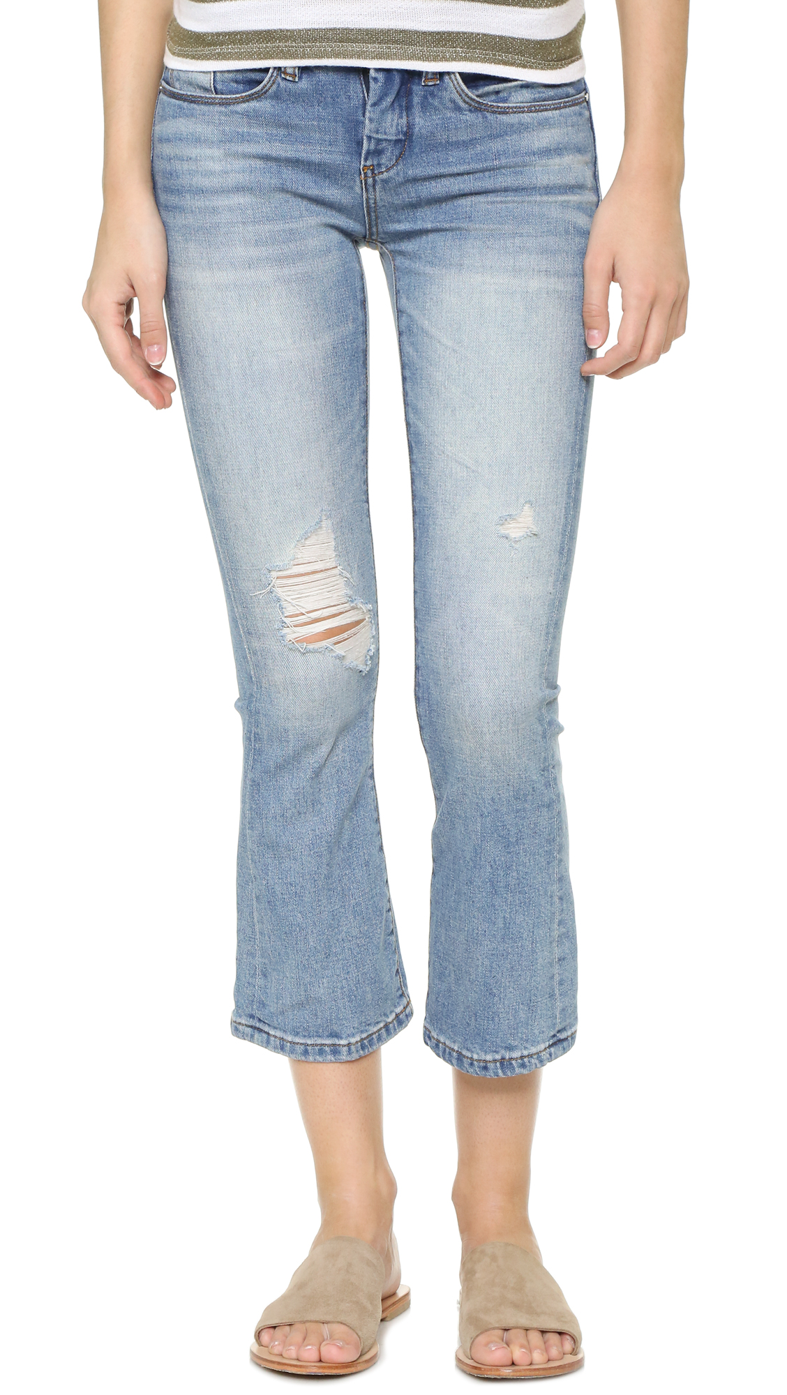 Feminine Blank Denim flares in faded, worn denim. Cropped silhouette with shredded detailing at the knees. 5 pocket styling. Button closure and zip fly. Fabric: Stretch denim. 98% cotton/2% spandex. Wash cold. Imported, China. Measurements Rise: 8in / 20.5cm