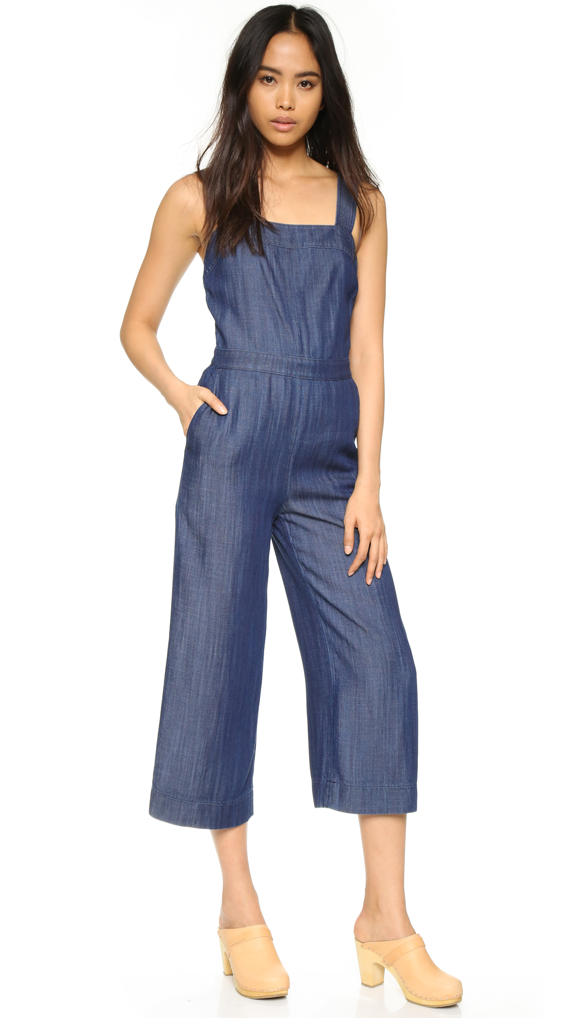 A cropped, slouchy Club Monaco jumpsuit in crisp denim. Slant hip pockets and welt back pockets. Sleeveless. Hidden back zip. Fabric: Denim. 100% lyocell. Wash cold or dry clean. Imported, China. Measurements Inseam: 22.75in / 58cm Leg opening: 23.5
