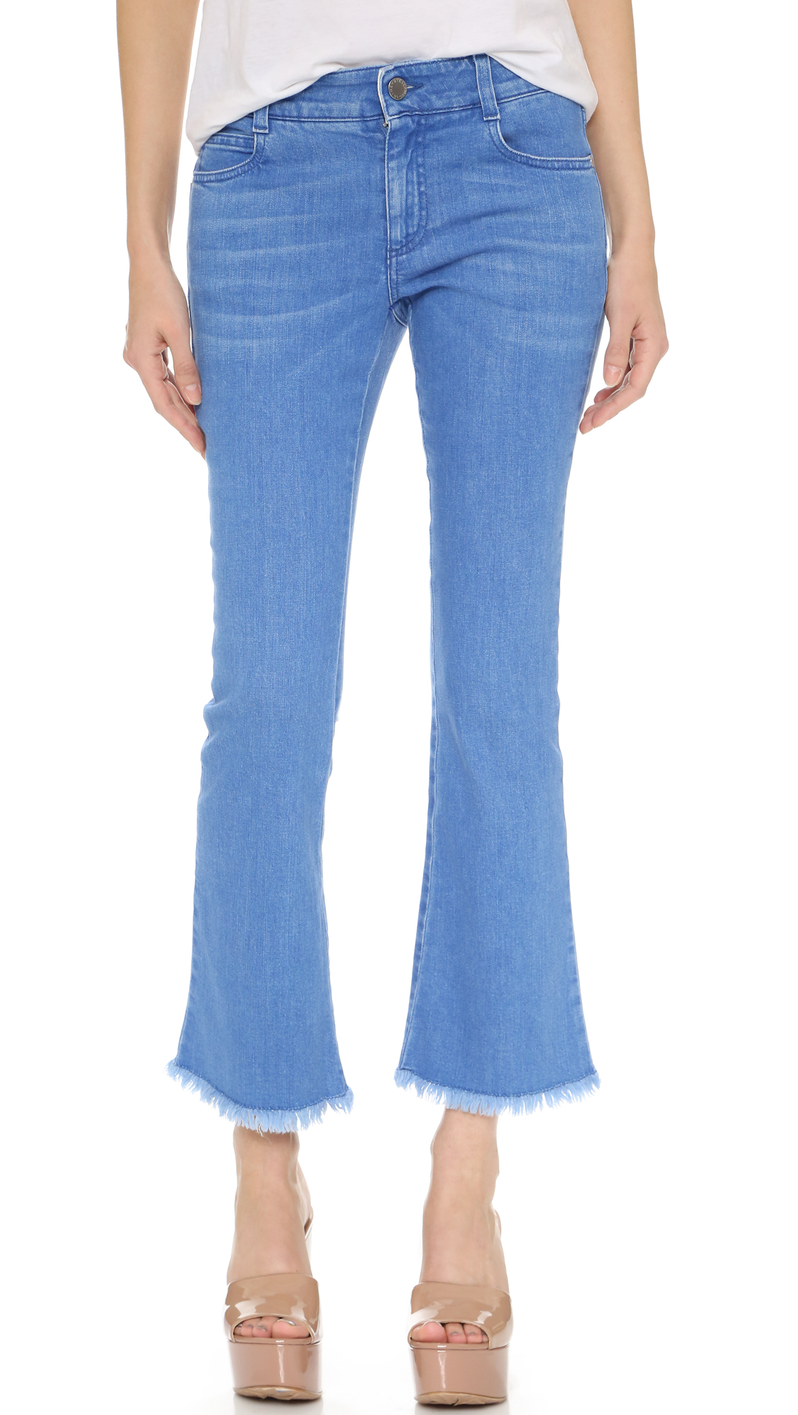 Runs small. Please see Size & Fit tab. Retro inspired Stella McCartney jeans in a saturated wash. The cropped silhouette has a flared, cutoff hem. Slight whiskering. 5 pocket styling. Button closure and zip fly. Fabric: Stretch denim. 98%