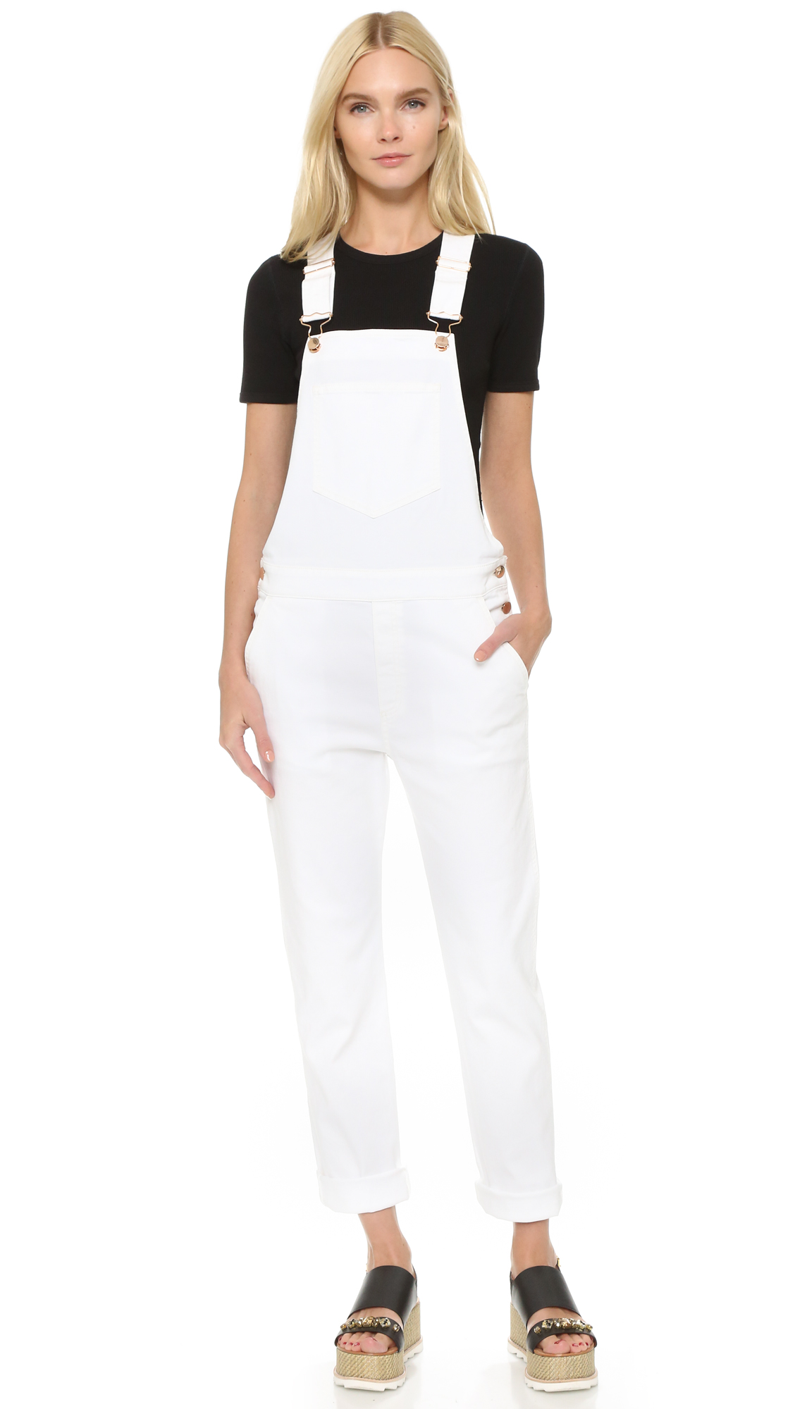 Polished buttons add a touch of shine to these crisp white Stella McCartney overalls. 5 assorted pockets. Adjustable straps. Fabric: Stretch denim. 98% cotton/2% elastane. Wash cold or dry clean. Made in Italy. Measurements Inseam: 29in / 73.5cm Leg