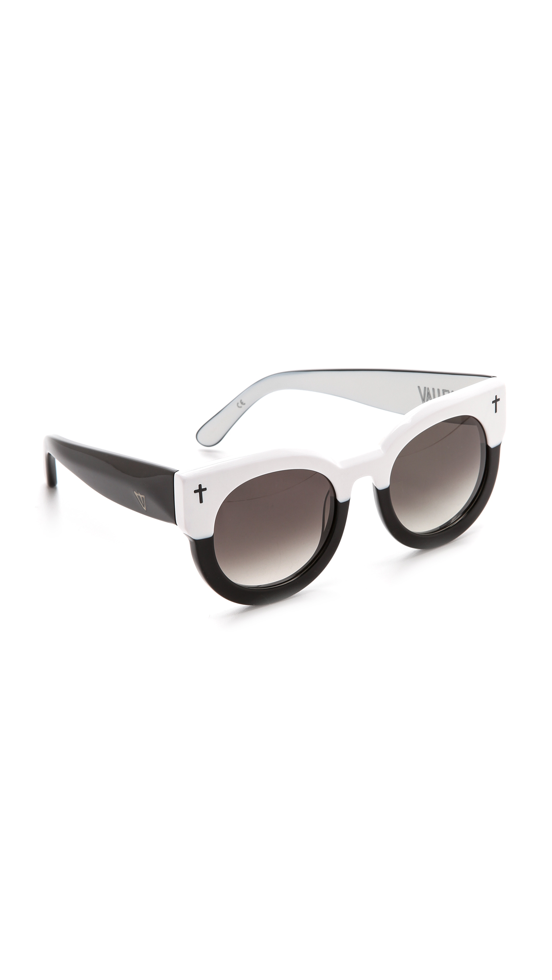 Striking Valley Eyewear sunglasses with glossy two tone frames. Small etched crosses detail the corners, and logo detailing accents the arms. Case and pouch included. Cateye frame. Non polarized lenses. Imported, China. Measurements Width: 5.75in / 14.5cm
