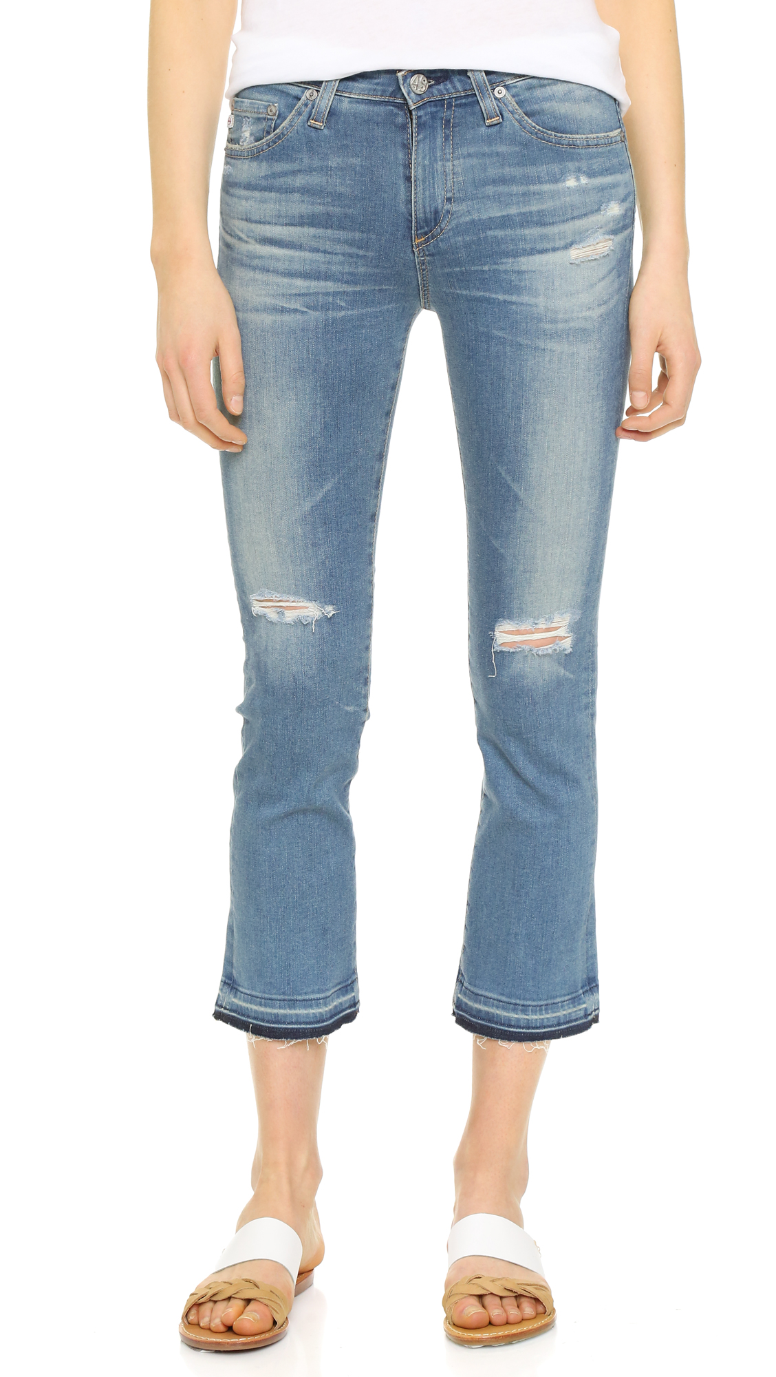 Raw, undone hems and shredded holes lend a well loved effect to these faded AG cropped jeans. 5 pocket styling. Button closure and zip fly. Fabric: Stretch denim. 98% cotton/2% polyurethane. Wash cold. Made in the USA. Imported