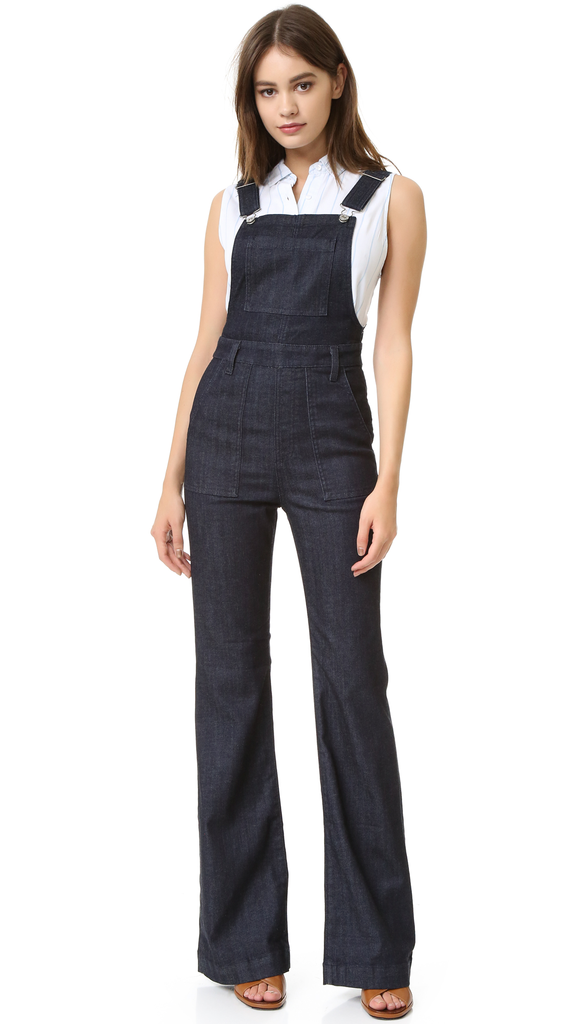 Flared AG overalls in a dark wash with 5 patch pockets. Exposed side zippers. Adjustable buckle shoulder straps. Fabric: Lightweight denim. 70% cotton/28% lyocell/2% polyurethane. Wash cold. Imported, Mexico. Measurements Inseam: 34.75in / 88cm Leg opening: 22in / 56cm Measurements