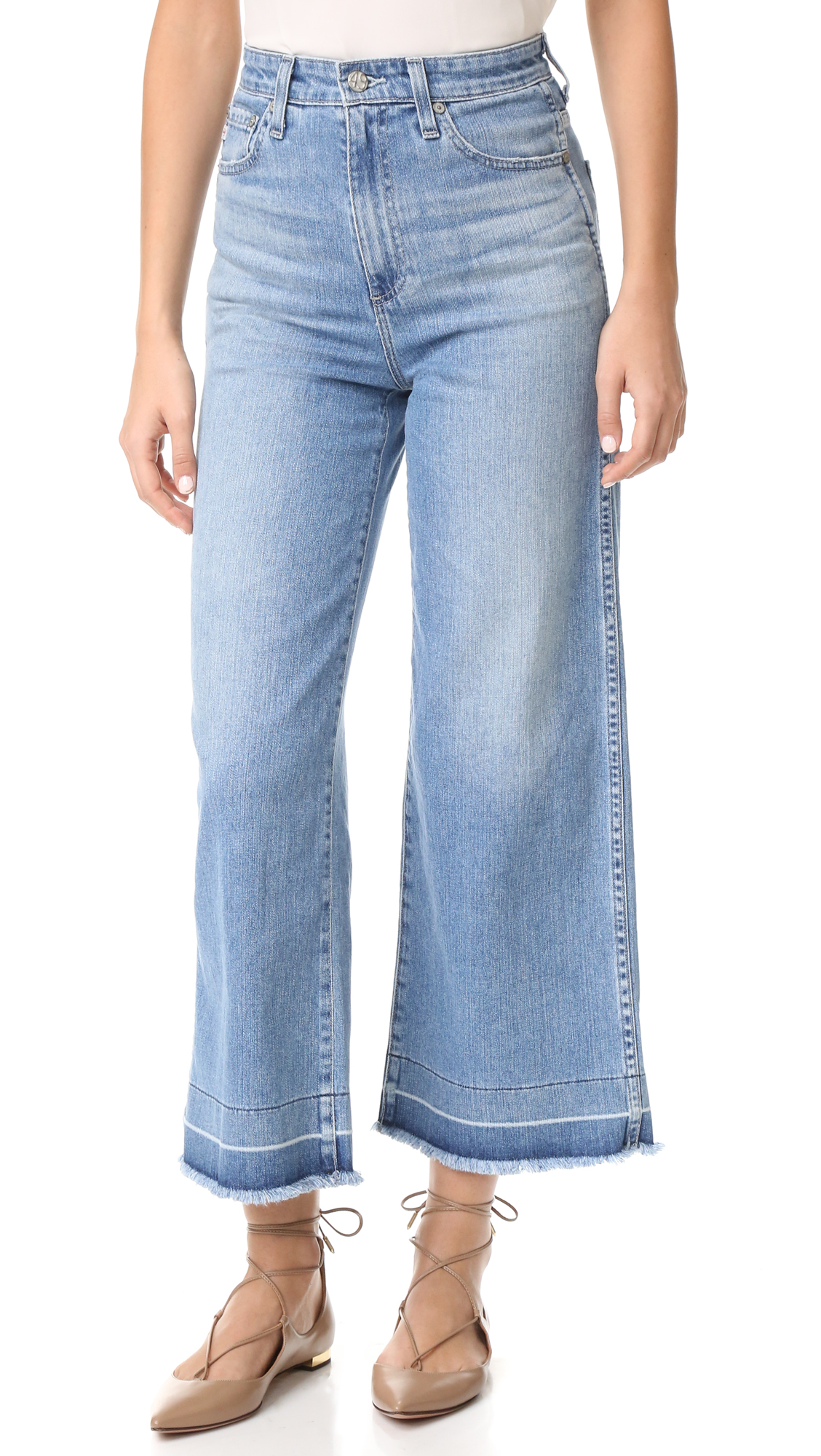 Undone hems lend a deconstructed feel to these high rise AG wide leg jeans. Heavy fading and fraying accentuate the well worn feel. 5 pocket styling. Button closure and zip fly. Fabric: Stretch denim. 98% cotton/2% polyurethane. Wash