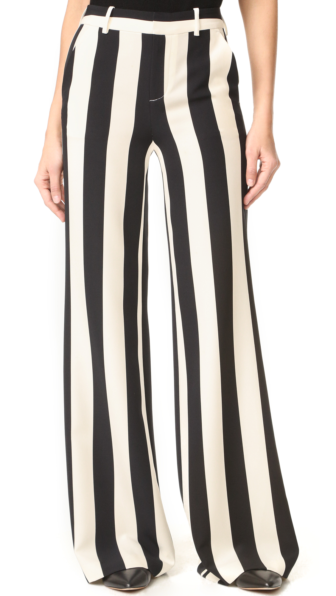 Wide, two tone stripes give these alice + olivia pants a bold, graphic look. High waisted, wide leg profile. Slant front pockets and welt back pockets. Hook and eye closure and zip fly. Fabric: Slinky crepe. 95% polyester/5%