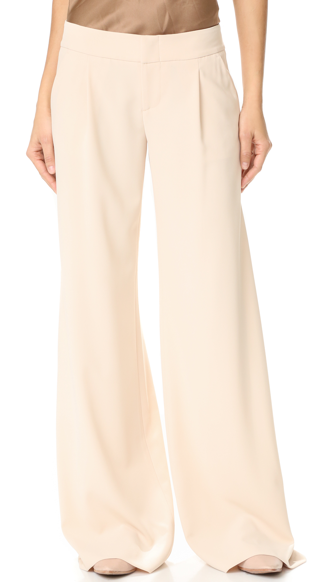 Deep pleats lend graceful movement to wide leg alice + olivia trousers. A wide waistband and 4 pockets complete the signature silhouette. Double hook and eye closure and zip fly. Fabric: Crepe suiting. 100% polyester. Wash cold or dry