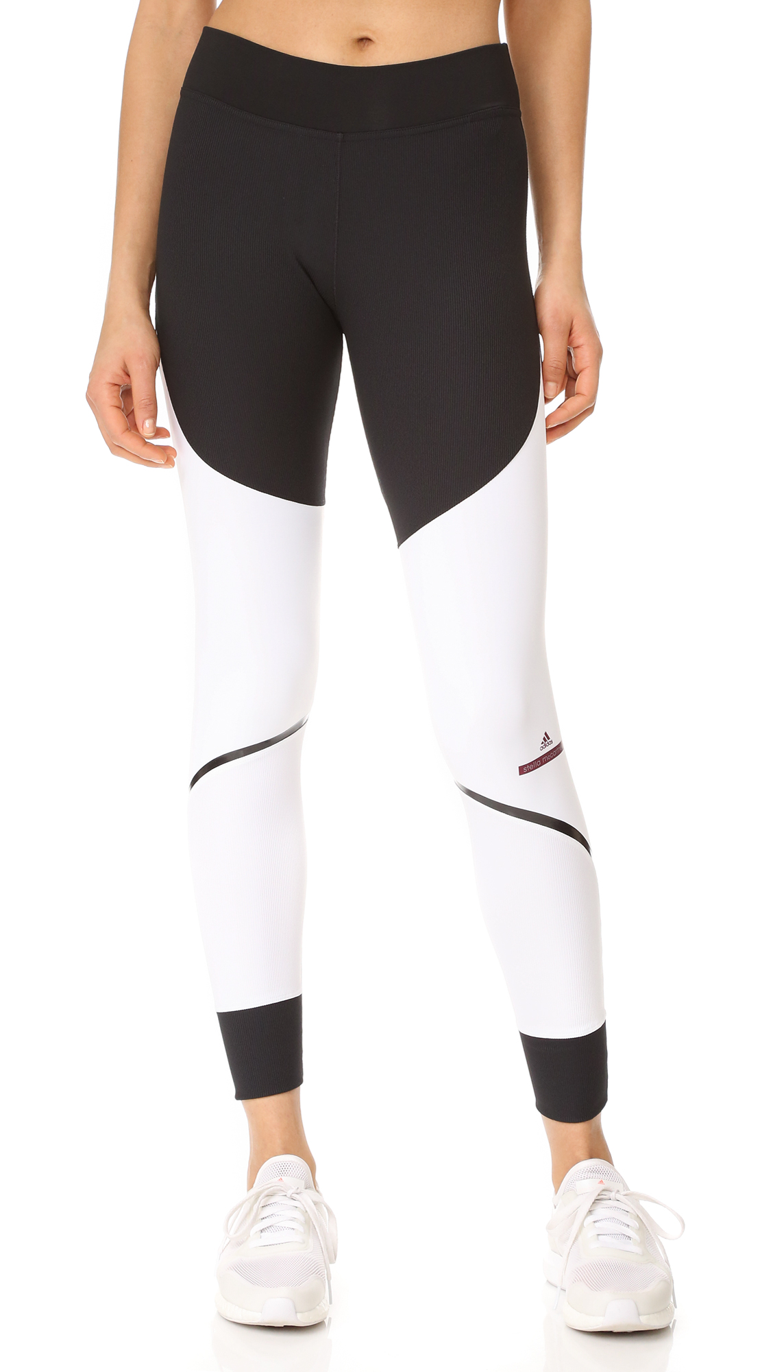 These two tone adidas by Stella McCartney leggings have reflective tape at the seams and an assortment of ribbed panels. Covered elastic waistband. Fabric: Activewear jersey. 80% polyester/20% spandex. Wash cold. Imported, Indonesia. Measurements Rise: 9.5in / 24cm