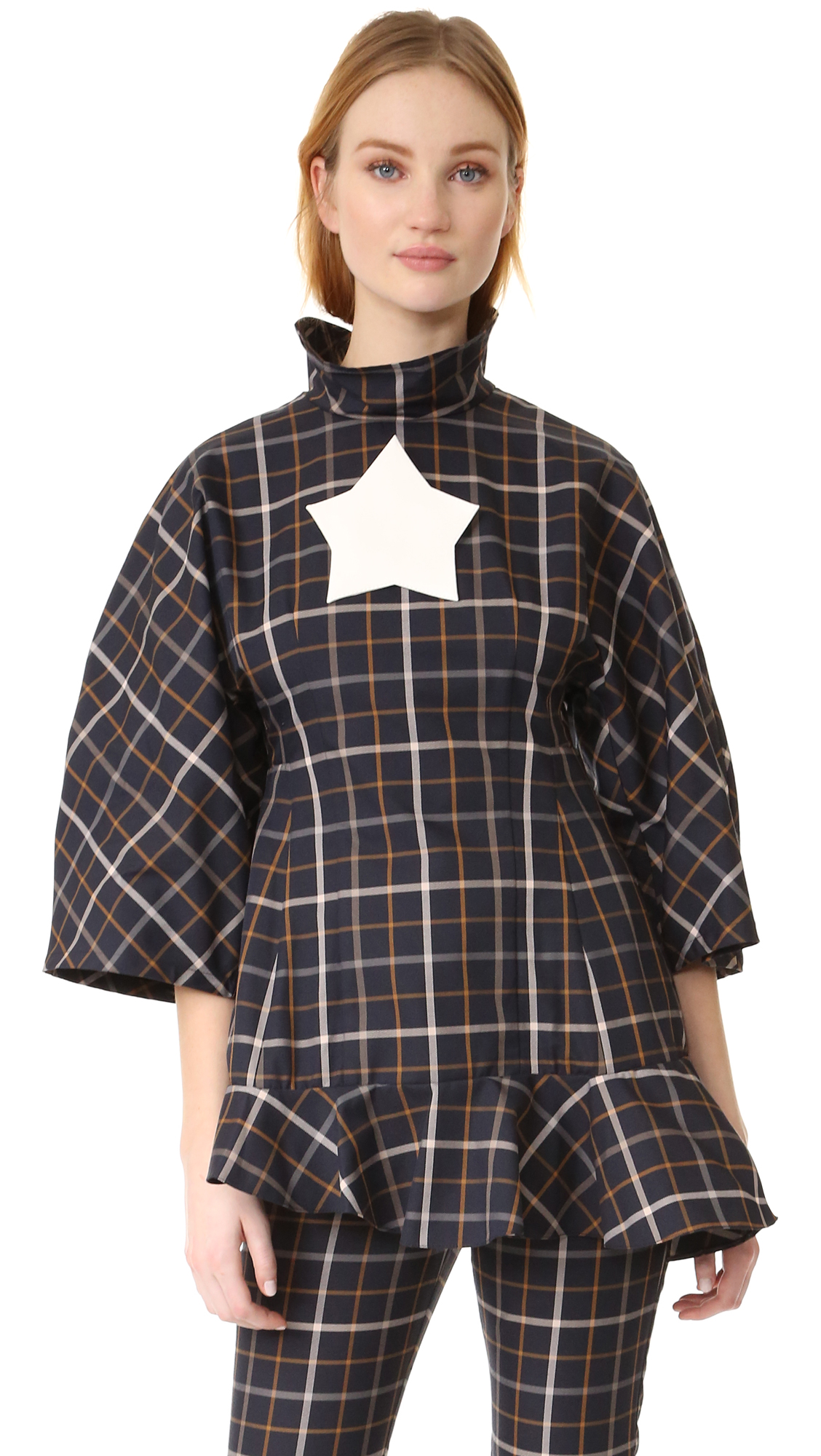 A checkered A.W.A.K.E. tunic plays with proportion with oversized sleeves and a flounced peplum hem. Optional star pin. Hidden back zip. Fabric: Mid weight weave. 58% cotton/42% polyester. Hand wash or dry clean.
