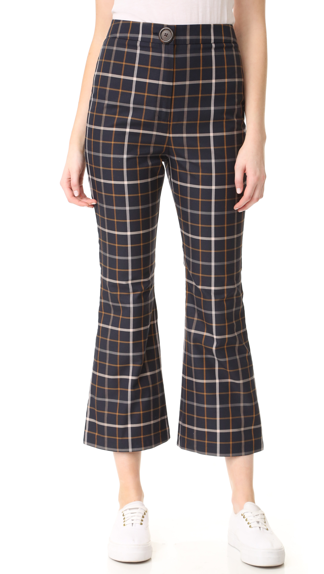 Clean plaid lends a graphic touch to these A.W.A.K.E. flared trousers. Button closure and zip fly. Fabric: Mid weight weave. 58% cotton/42% polyester. Hand wash or dry clean. Made in United Kingdom. Measurements
