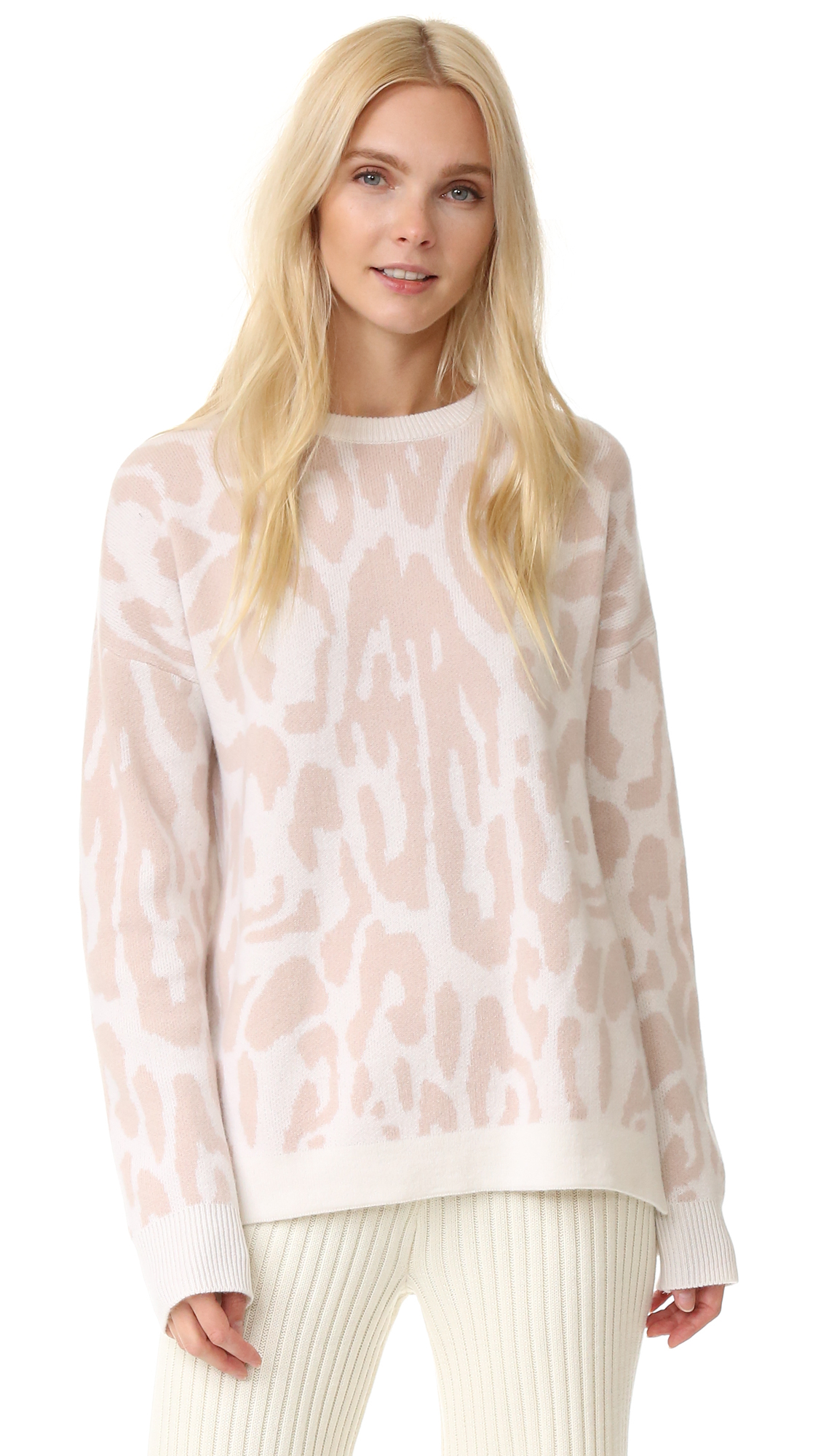Pastel leopard spots accent this plush cashmere Baja East sweater. Dropped shoulder seams and a split hem relax the fit. Crew neckline. Long sleeves. Fabric: Soft double knit. 100% cashmere. Hand wash or dry clean. Made in