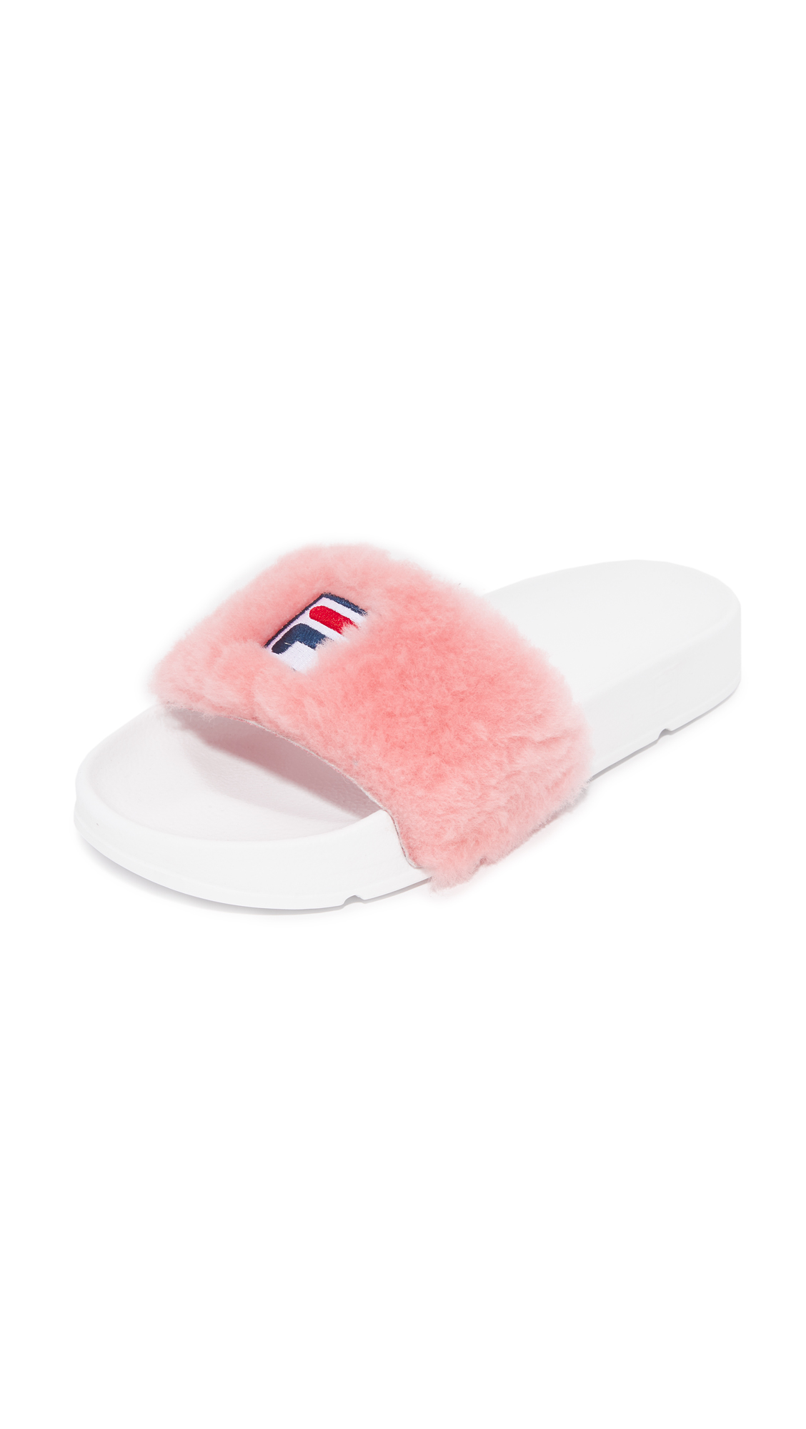 A part of the Baja East x Fila collaboration, these shearling Baja East slides are detailed with embroidered Fila logo patches. Molded footbed and rubber sole. Fur: Dyed sheep shearling, from China. Imported, China. Size & Fit.