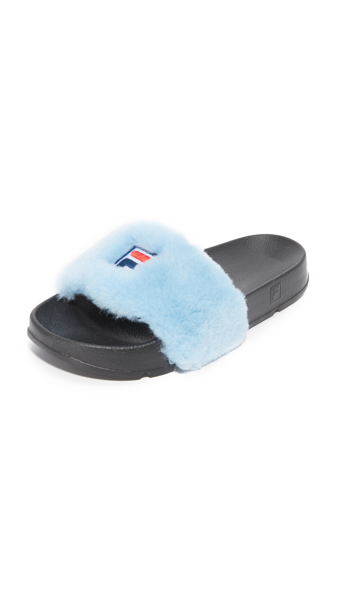 These plush fur FILA x Baja East slides blend luxury with athletic style. Molded foam rubber footbed. Rubber sole. Fur: Dyed sheep shearling, from China. Imported, China. Measurements Platform: 1.25in / 30mm THIS ITEM CANNOT BE SHIPPED