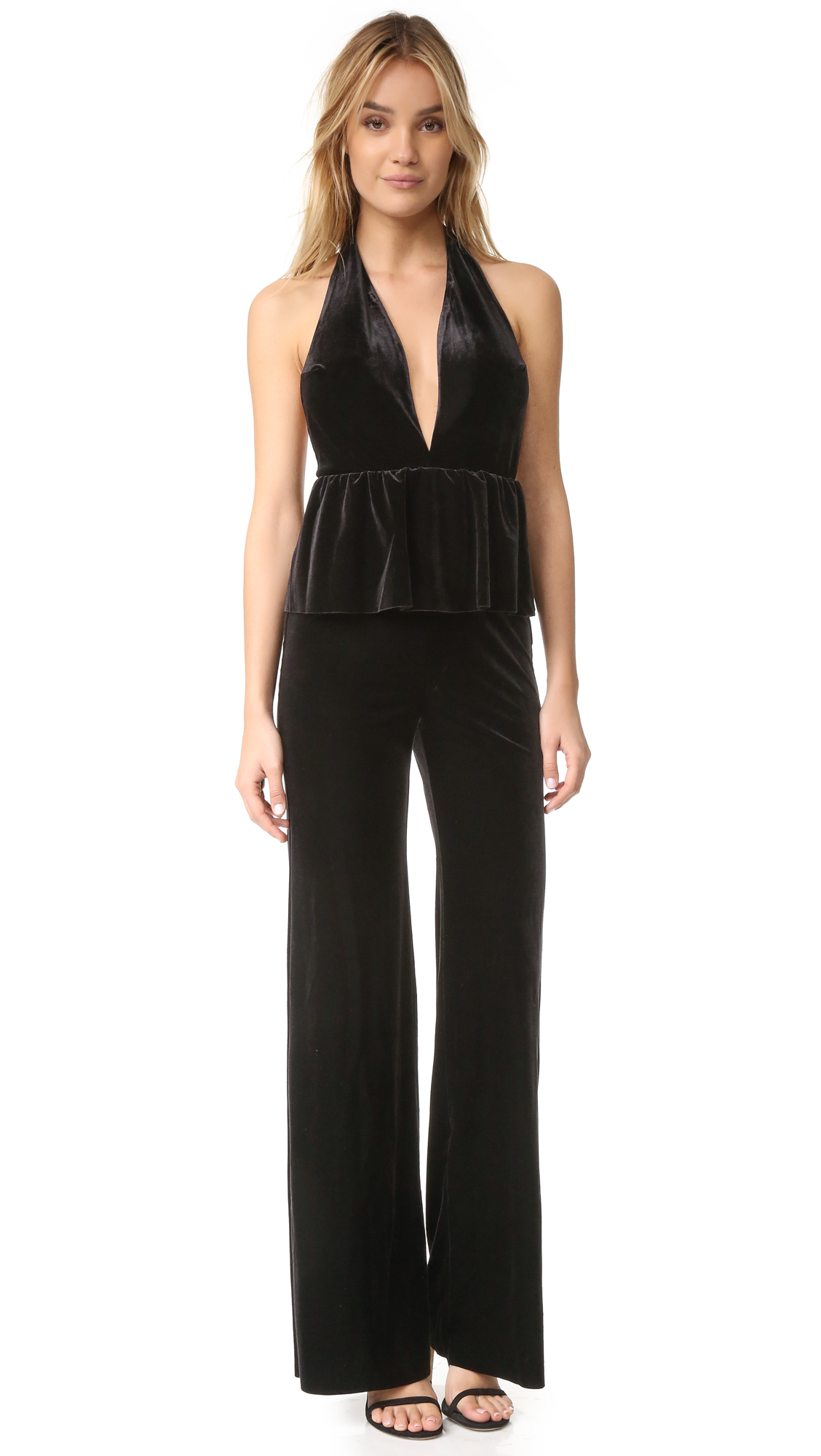 A velour Bec & Bridge jumpsuit in a fluid, wide leg silhouette. The halter bodice is styled with a plunging V neckline and a flounced ruffle at the waist. Raw hems. Hidden back zip. Fabric: Velour. Shell: 90%