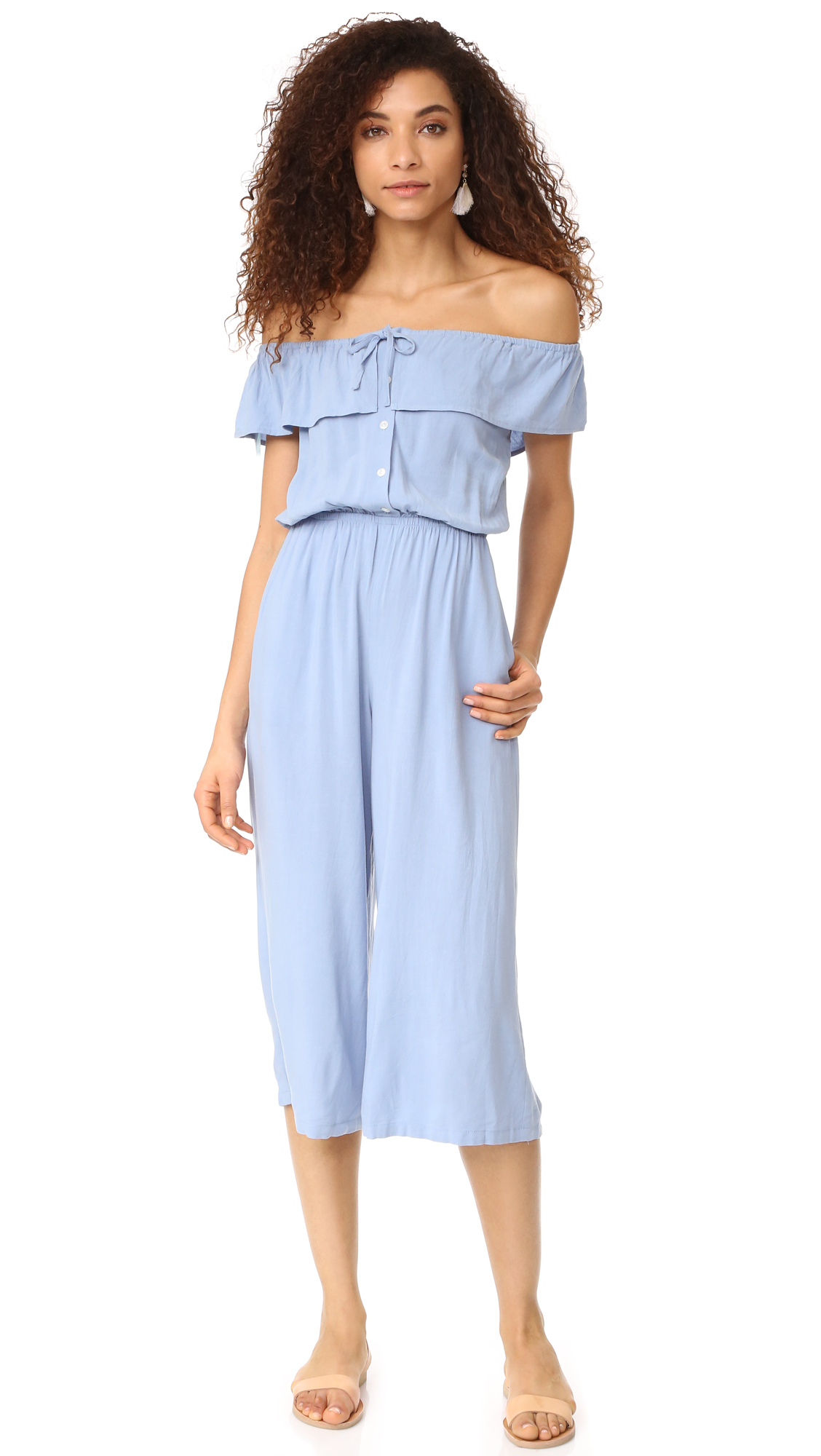 A lightweight Capulet jumpsuit with a flirty off shoulder profile. Ties and a short overlay accent the elastic neckline. Gathered elastic waistband. On seam pockets. Button half placket. Fabric: Crepe. 85% viscose/15% linen. Dry clean. Imported, China.