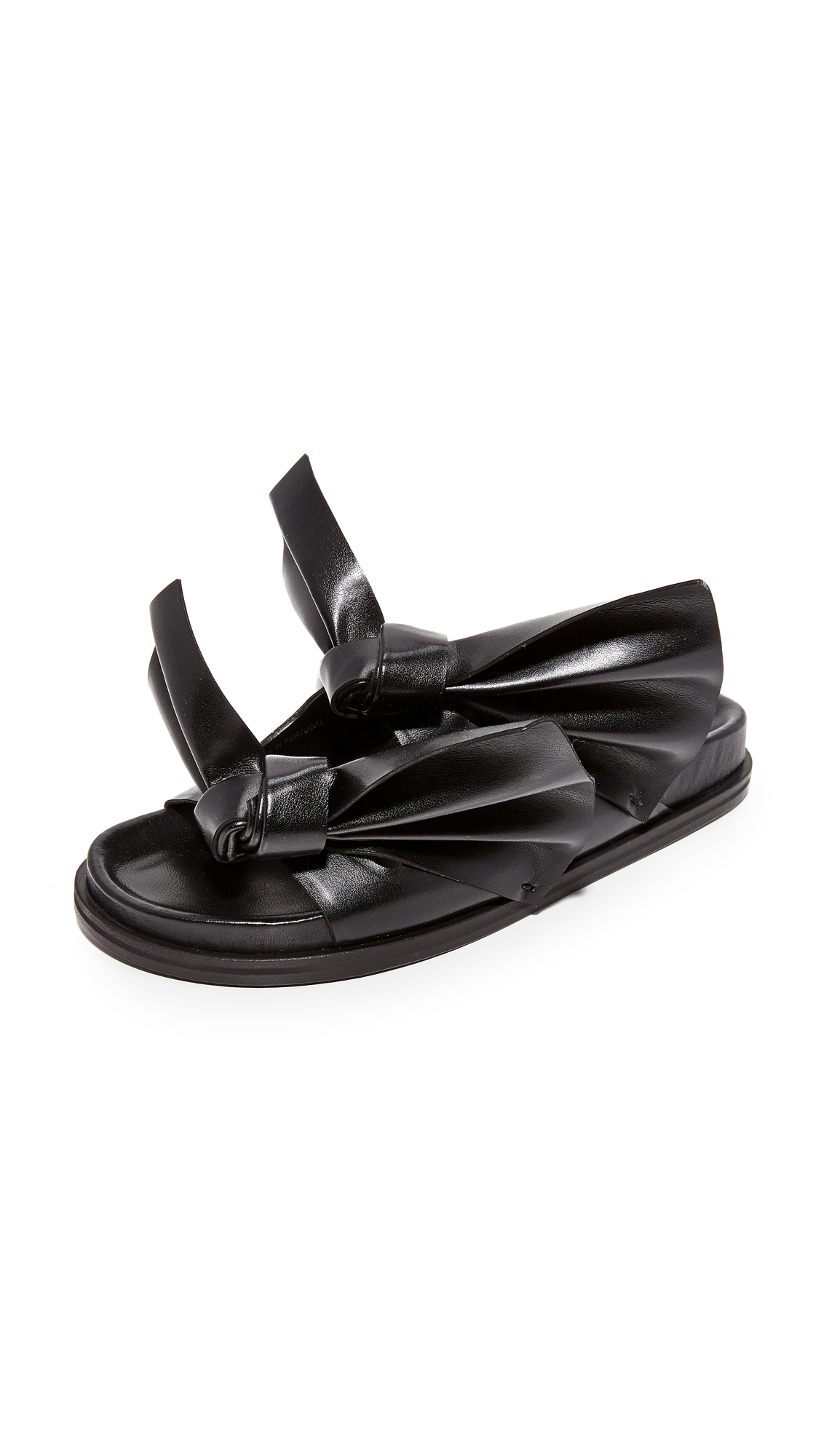 Dramatic, knotted bows detail the vamp on these faux leather Cedric Charlier slides. Molded footbed and stacked platform. Leather sole. Fabric: Faux leather. Made in Portugal. Size & Fit. Available sizes: 36,37,38,39,40,41