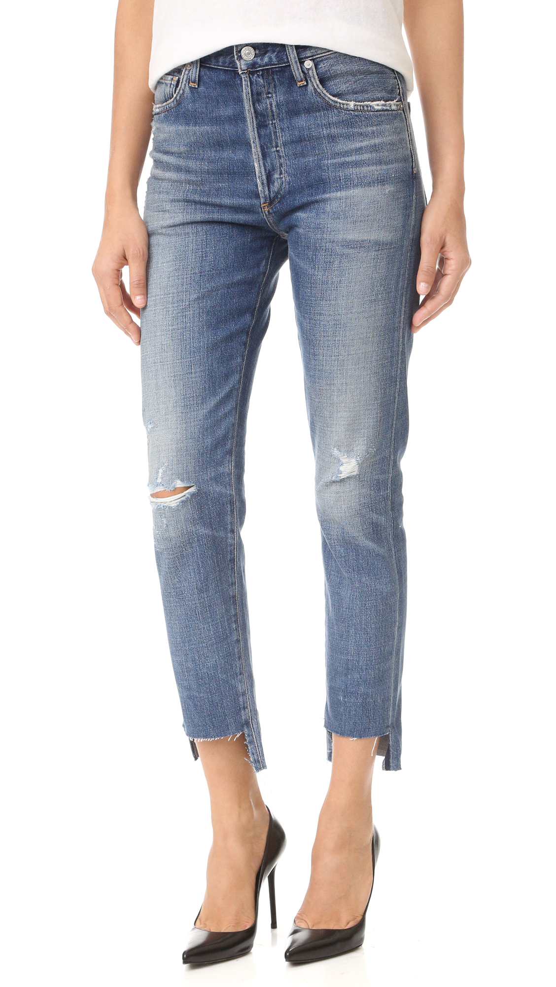 Raw, notched hems lend a hand cropped look to these heavily worn and faded Citizens of Humanity jeans. 5 pocket styling. Button fly. Fabric: Lightweight denim. 77% cotton/23% rayon. Wash cold. Made in the USA. Imported materials. Measurements