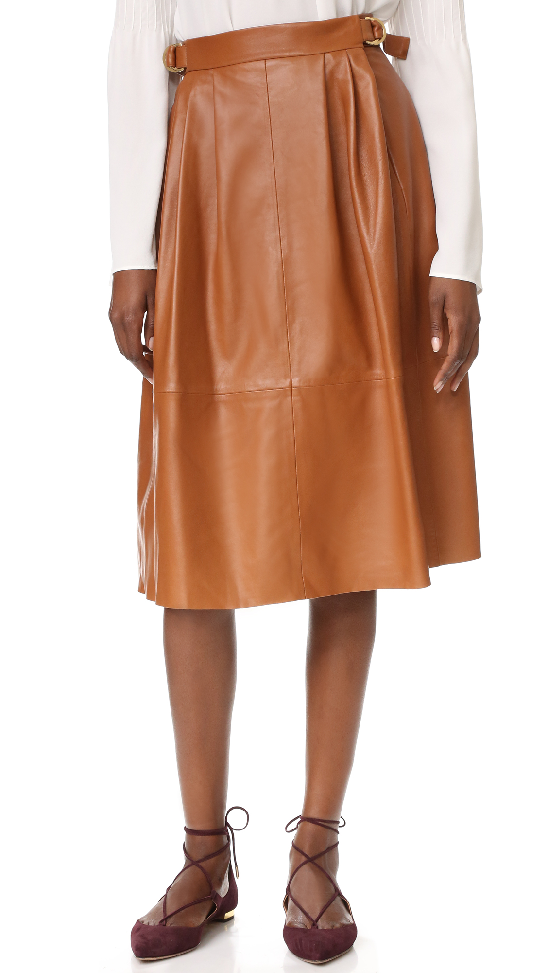 A chic Derek Lam skirt in buttery leather. Gold tone D ring buckles cinch the straps at the hips. On seam hip pockets. Lined. Fabric: Soft leather. Shell: 100% lambskin. Lining: 52% viscose/48% cotton. Dry clean. Made in