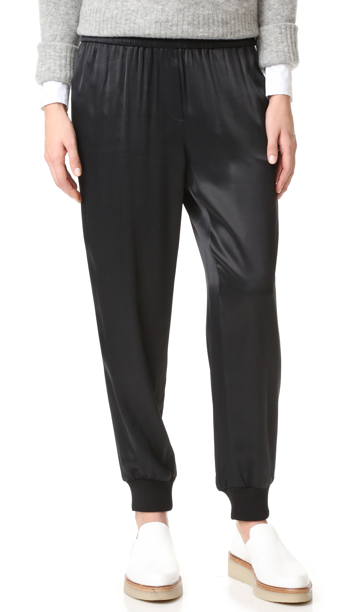 Glossy, pull on DKNY pants styled with a faux fly and ribbed cuffs. Side pockets and welt back pockets. Smocked elastic waistband. Fabric: Technical weave. 100% viscose. Dry clean. Imported, China. Measurements Rise: 11.25in / 28.5cm Inseam: 26.5in / 67