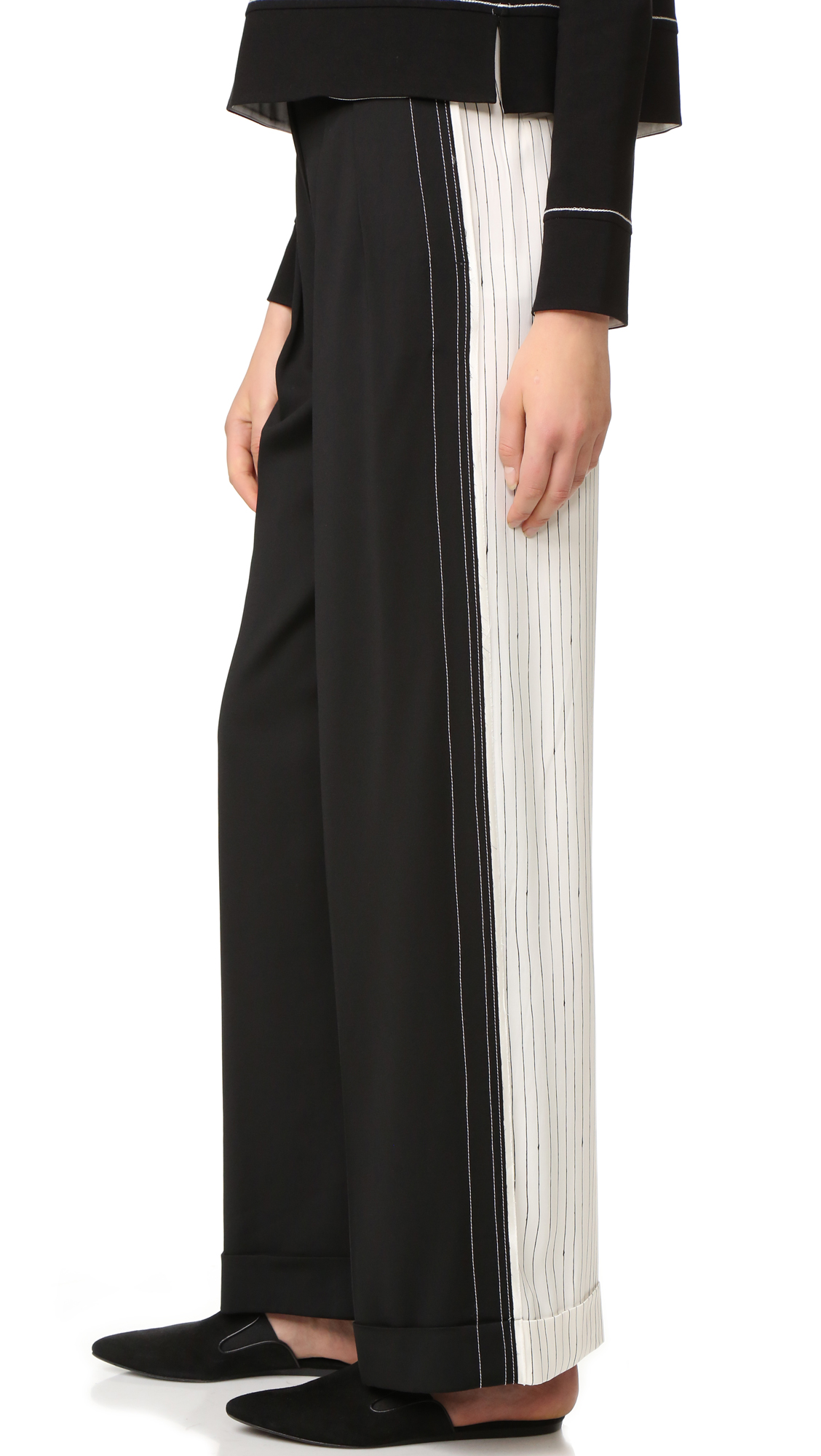 Pleated, high rise DKNY trousers are solid in the front and striped in back. Raw side seams lend a deconstructed feel to the wide leg silhouette. Fixed, rolled cuffs. Welt back pockets. Extended tab hook and