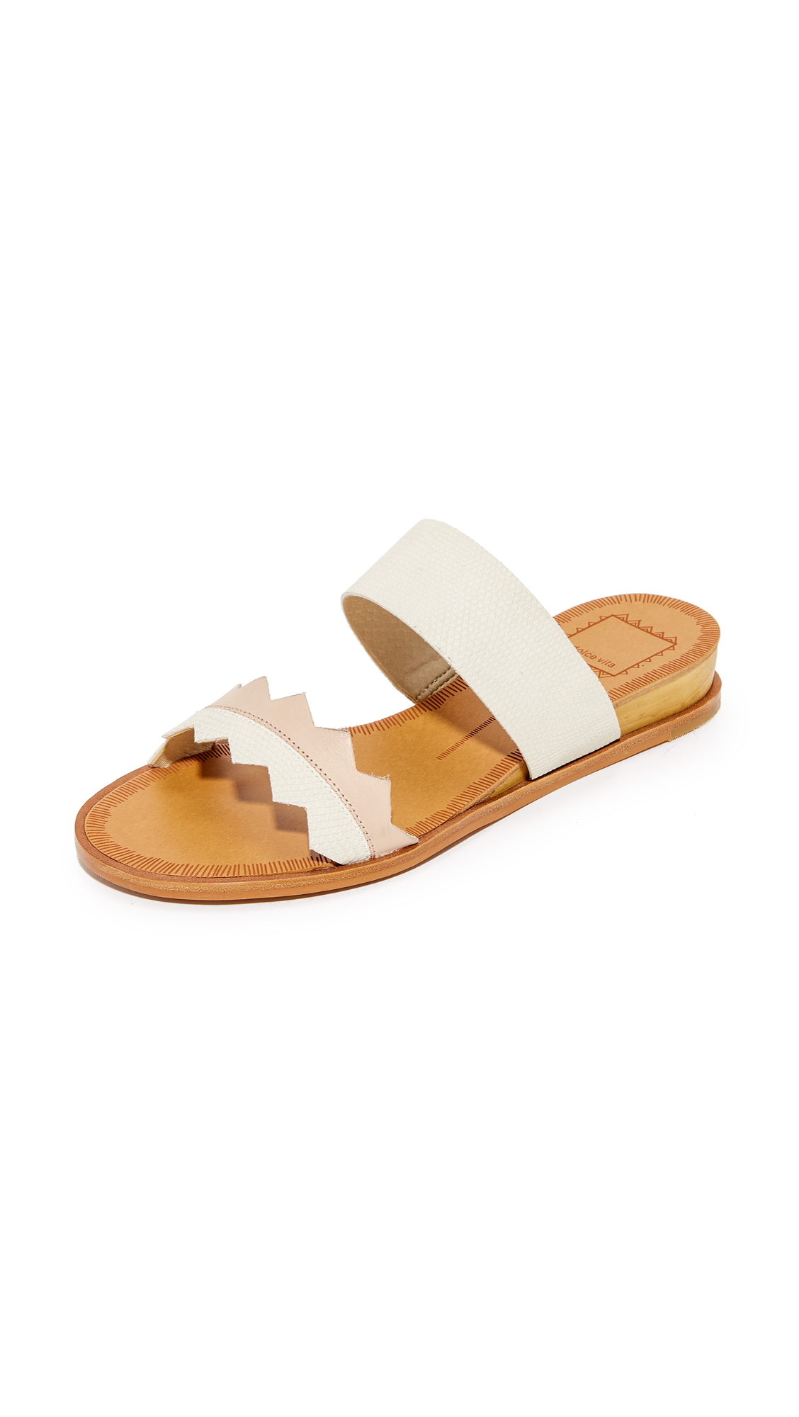 Mixed texture panels of faux and real leather lend a tactile touch to these Dolce Vita slide sandals. Low wood wedge heel. Man made sole. Fabric: Faux leather. Leather: Cowhide. Imported, China. This item cannot be