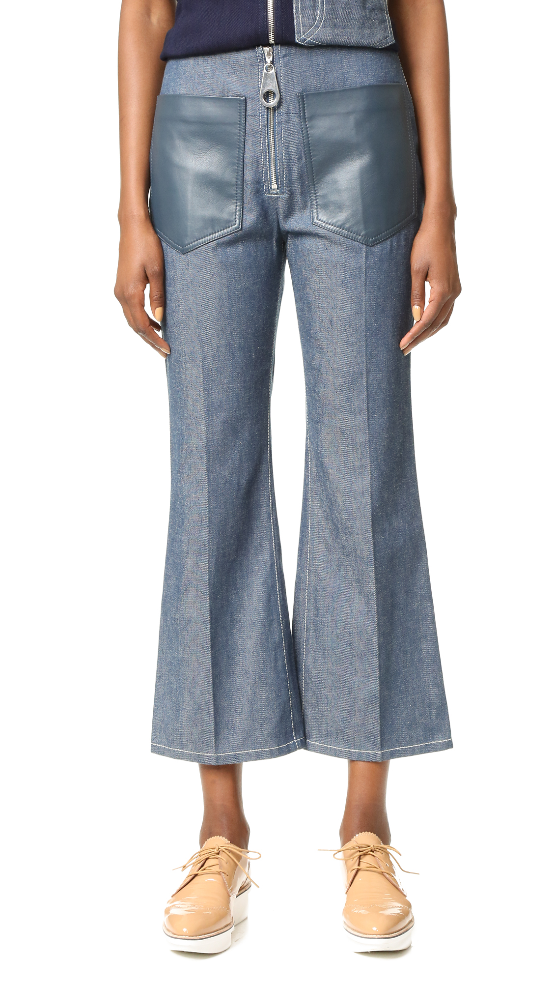 High rise EDUN denim pants with a cropped, slightly flared profile. Tonal leather patch pockets and exposed zip fly. Contrast reinforced topstitching. Fabric: Raw denim. Shell: 100% cotton. Trim: 100% lambskin. Leather clean. Imported, Kenya. Measurements Rise: 4.75in / 12