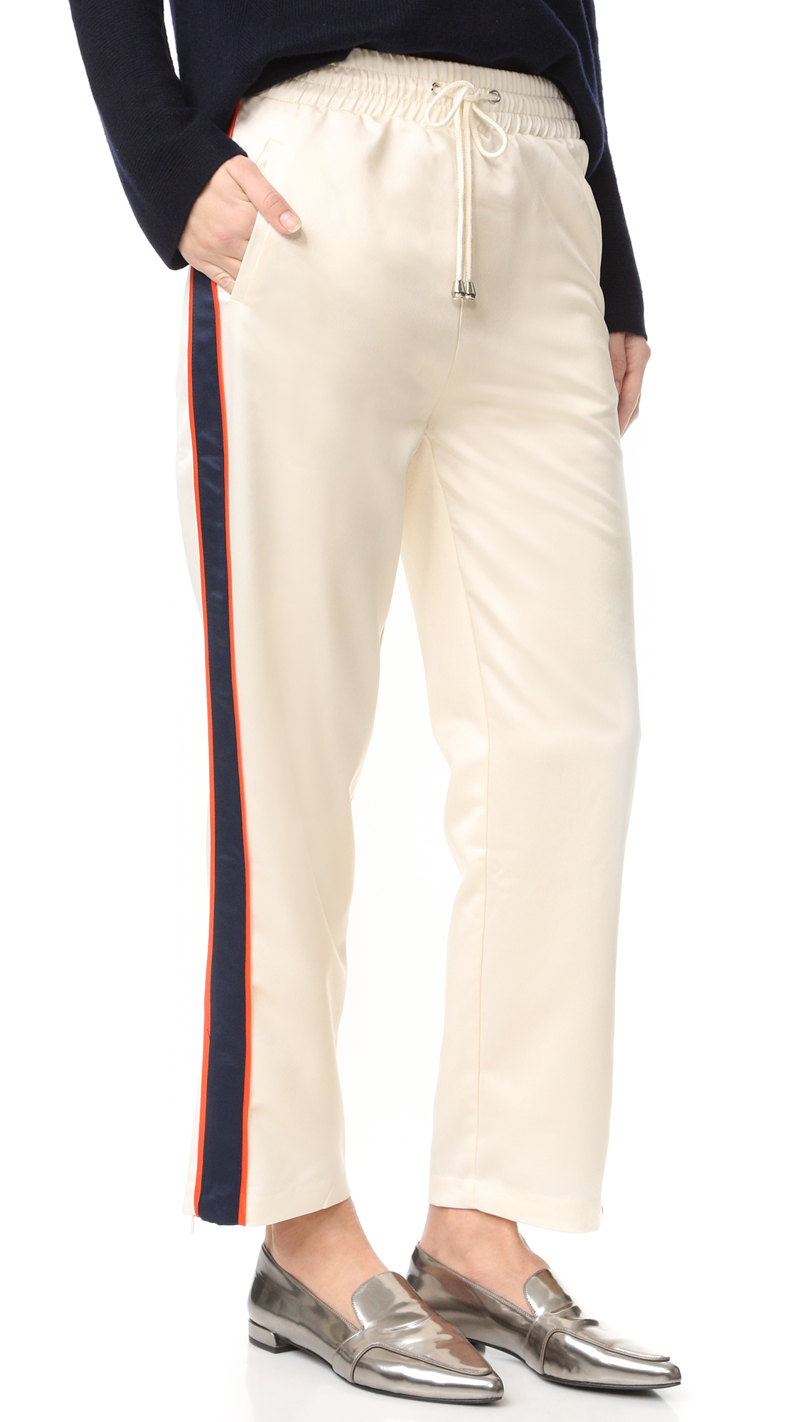 Bold tuxedo stripes add a sporty touch to these lustrous satin endless rose pants. A drawstring cinches the smocked elastic waistband. Welt hip pockets and faux back pockets. Hidden ankle zips. Fabric: Satin. 100% polyester. Hand wash.