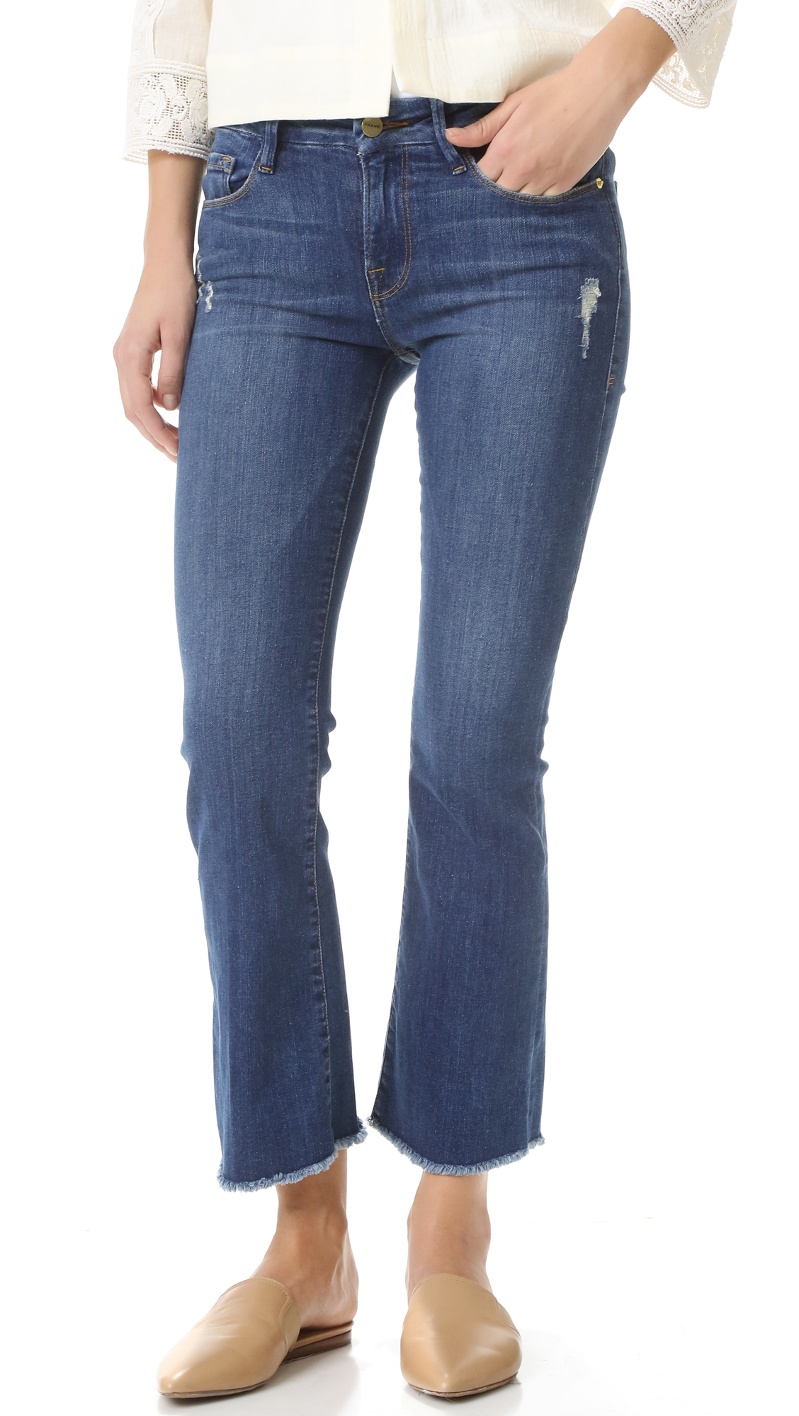 Sleek, super stretch FRAME cropped jeans with raw edged cuffs and a subtle flared cut. 5 pocket styling. Button closure and zip fly. Fabric: Super stretch denim. 93% cotton/5% polyester/2% elastane. Wash cold. Made in the USA. Imported