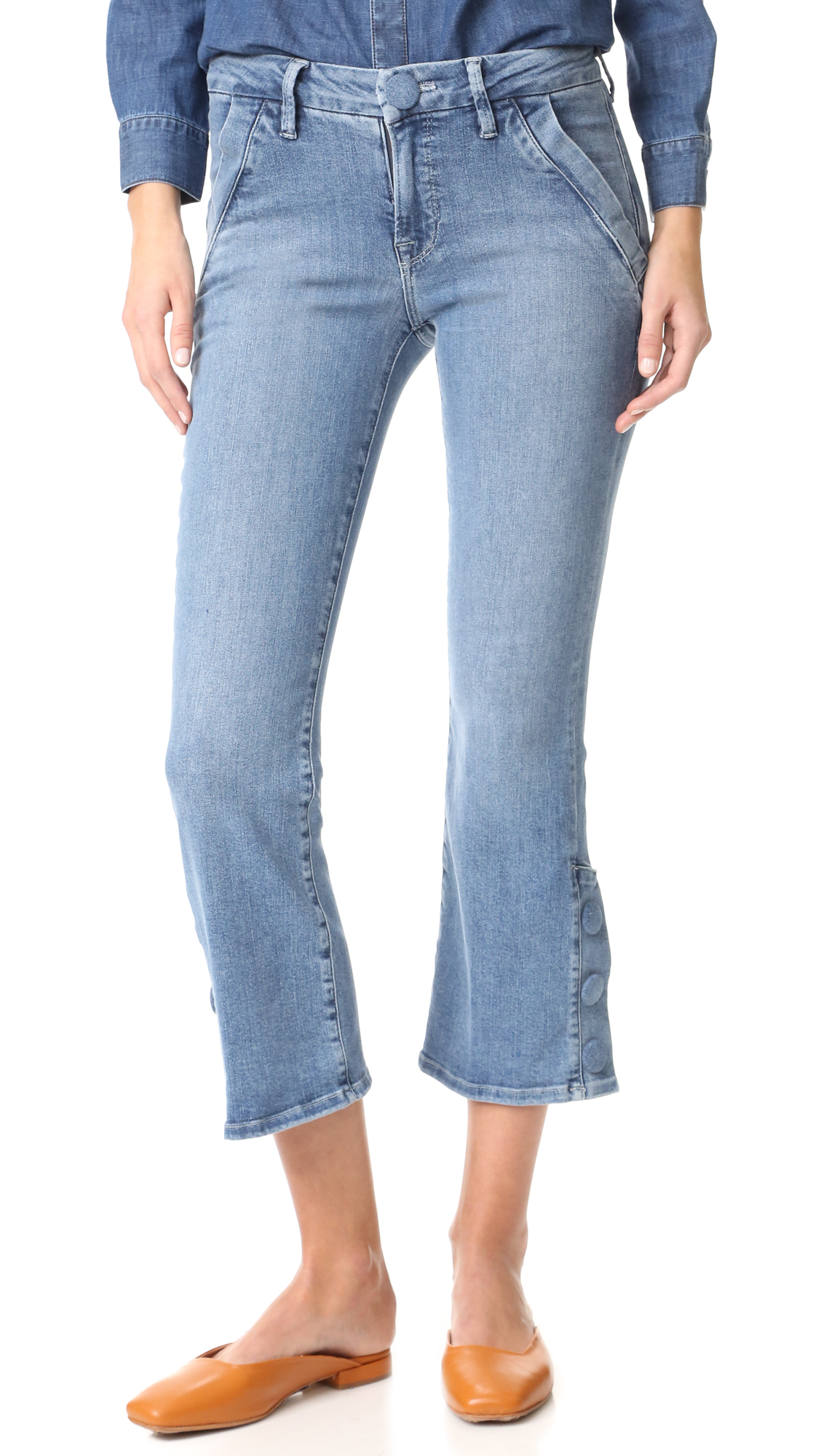 Soft stretch denim lends a curve conforming fit to these ankle length FRAME jeans. Bold snaps detail the hem. Slant hip pockets and welt back pockets. Button closure and zip fly. Fabric: Stretch denim. 68.5% cotton/25% tencel/5%