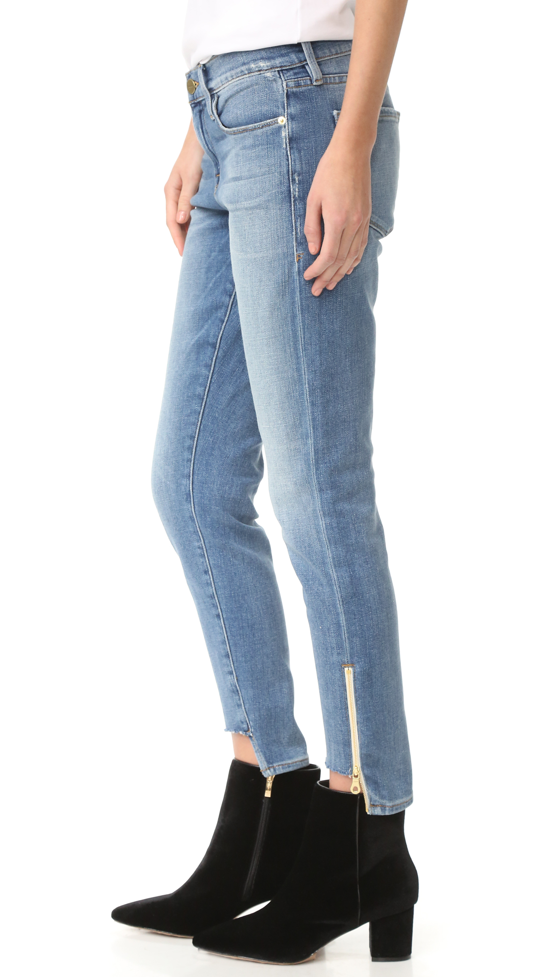 Slouchy, faded FRAME jeans with gold tone zippers at the cutaway cuffs. 5 pocket styling. Button closure and zip fly. Fabric: Soft stretch denim. 94% cotton/5% polyester/1% spandex. Wash cold. Made in the USA. Measurements Rise: 9.5in / 24cm