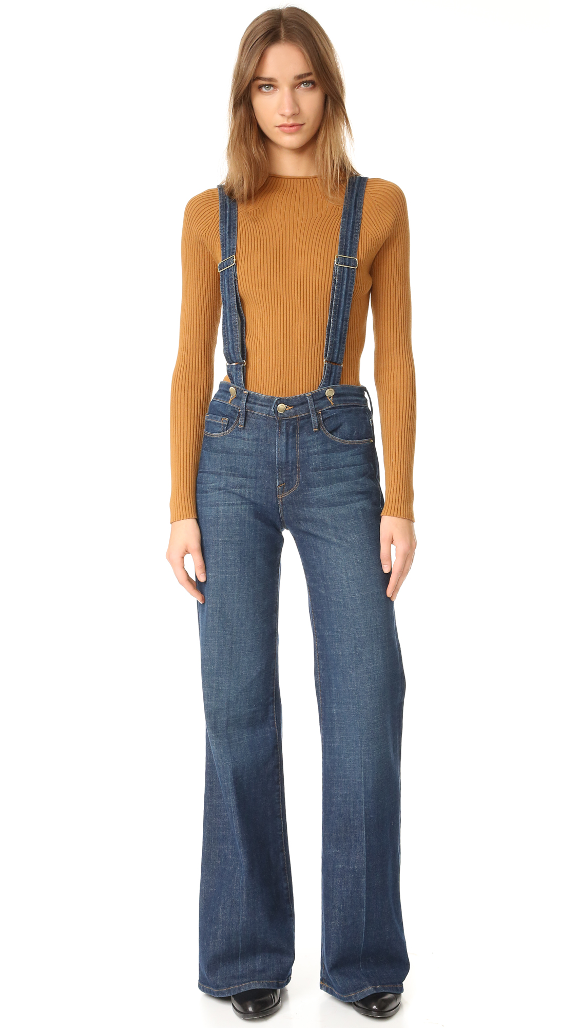 Attached, adjustable suspenders lend rustic charm to these high waisted FRAME wide leg jeans. 5 pocket styling. Button closure and zip fly. Fabric: Soft stretch denim. 93.5% cotton/5% polyester/1.5% elastane. Wash cold. Made in the USA. Imported materials.