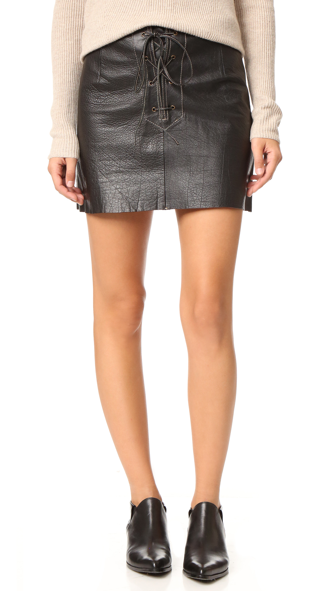 A wrinkled leather Free People mini skirt with a lace up front and contrast stitching. Raw hem. Unlined. Fabric: Leather. 100% cowhide. Leather clean. Imported, India. Measurements Length: 14.25in / 36cm Measurements from size 4. Available sizes: 2,8